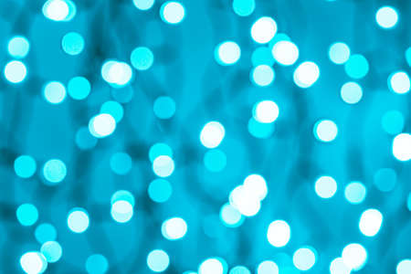 Bokeh cyan blue led lighting abstract blurred background. Defocused blue lights of an electric garland. Decoration and design element for holidays concepts. Copy space. Full frame.