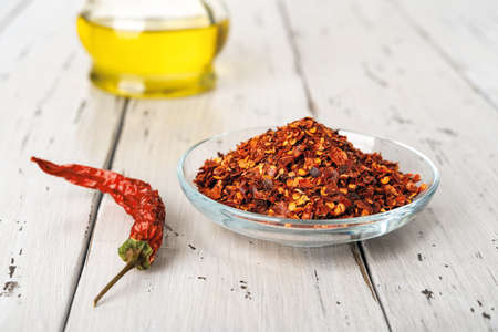 Red hot pepper flakes in a glass saucer and dry wrinkled pepper pod on a rustic wood table. Natural spices and seasonings for meat, fish and vegetables dishes. Front view. 免版税图像