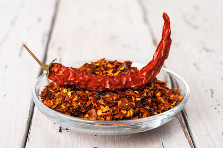 Dry wrinkled pod of red hot pepper on a heap of pepper flakes in a glass saucer on a rustic wood table. Natural spices and seasonings for meat, fish and vegetables dishes. Front view.