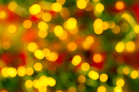 Bokeh yellow led lighting on a blurred red green background. Defocused lights of an electric garland. Decoration and design element for holidays concepts. Copy space. Full frame. 免版税图像