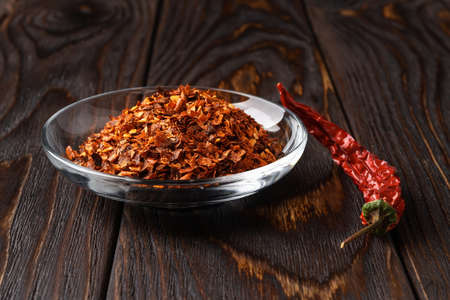 Red hot pepper flakes in a glass saucer and dry wrinkled pod on a dark wood table. Natural spices and seasonings for meat, fish and vegetables dishes. Low key image. Front view.