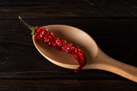 Dry pod of red chilli pepper in a large wooden spoon on a black wood table close-up. Natural spices and seasonings for meat, fish and vegetable dishes. Low key image. Top view. 免版税图像