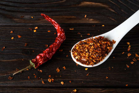 Hot chilli pepper flakes in a white porcelain spoon and red dry pepper pod on a black wood table. Natural spices and seasonings for meat, fish and vegetable dishes. Low key image. Top view.