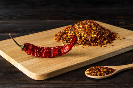Red chilli pepper dry pod and flakes on a cutting board over black wood table. Natural spices and seasonings for meat, fish and vegetable dishes. Low key image. Front view.