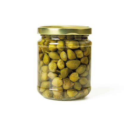 Full glass jar of pickled capers in a brine isolated on white background. Marinated buds of caper bush. Mediterranean cuisine ingredient. Organic spices and seasonings for meat, fish and vegetables. Front view. 免版税图像