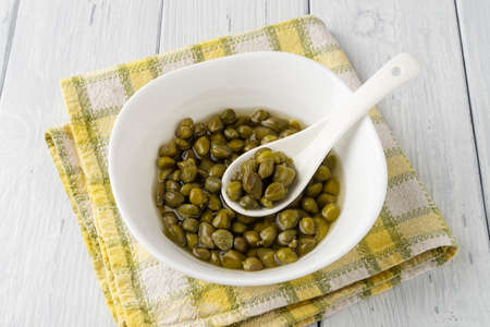 Pickled capers in a brine and porcelain spoon in a white bowl on a white wood rustic table. Marinated buds of caper bush. Mediterranean cuisine ingredient. Organic spices and seasonings. Top view. 免版税图像
