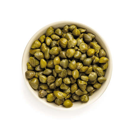 Pickled capers in a beige bowl isolated on white background. Marinated buds of caper bush. Mediterranean cuisine ingredient. Organic spices and seasonings for meat, fish and vegetables. Top view.