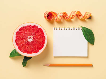 Half of ripe juicy grapefruit, roll of measuring tape, spring notepad and pensil on a pastel yellow background. Slimming diet, body weight control and healthy eating. Copy space. Top view. 免版税图像