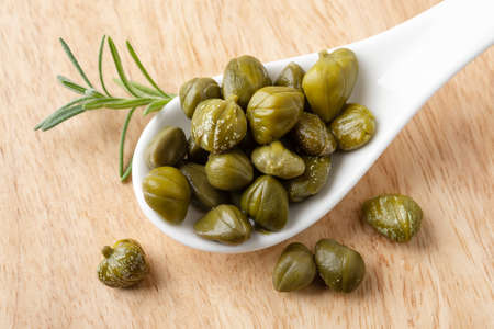 Pickled capers in a white porcelain spoon on a brown wooden cutting board. Marinated buds of caper bush. Mediterranean cuisine ingredient. Organic spices and seasonings. Top view.