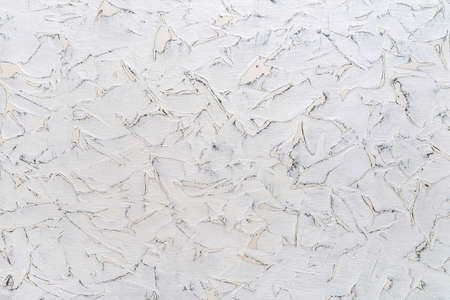 Texture of cracked white paint on a surface with spots of different shapes. White aged wall with gray scratches. Abstract construction background design element. Front view. 免版税图像