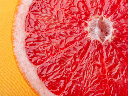 Slice of ripe juicy grapefruit on a yellow background macro shot. Ingredient for fruit desserts. Tasty vegetarian food, slimming diet and vitamin healthy eating. Close-up. Front view.