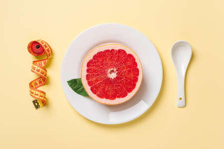 Half of ripe juicy grapefruit on a white plate,  white spoon and roll of measuring tape on a pastel yellow background. Slimming diet, body weight control and healthy eating. Top view.