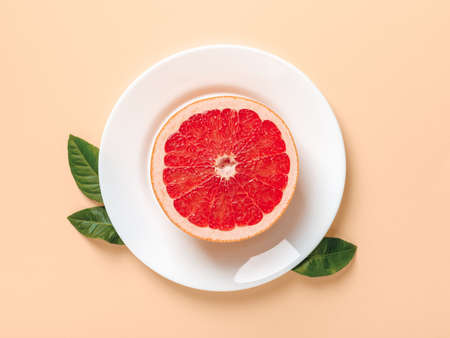 Half of ripe juicy grapefruit on a white plate and few green leaves on a beige background. Slimming diet, body weight control and vitamin healthy eating. Top view. 免版税图像