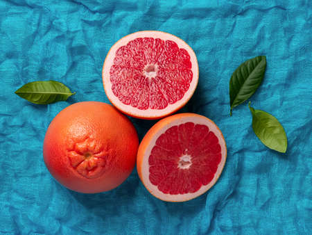 Whole ripe grapefruit and two juicy halves on a turquoise cloth background. Ingredient for fruit desserts. Tasty vegetarian food, slimming diet and vitamin healthy eating. Top view.