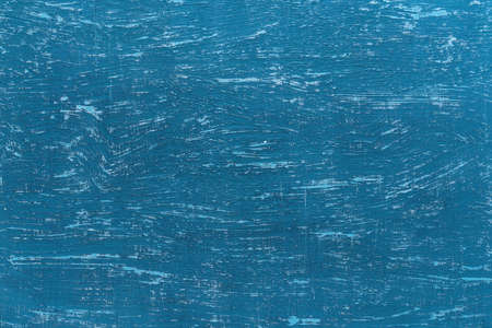 Texture of scratched blue paint on an old rough painted surface. Blue aged wall with turquoise scratches. Abstract construction background design element. Front view.