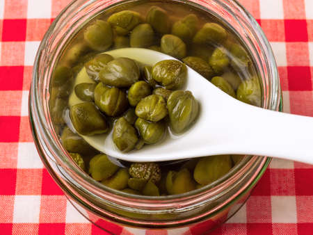 Taking pickled capers from a glass jar with white porcelain spoon close-up. Marinated buds of caper bush. Mediterranean cuisine ingredient. Organic spices and seasonings. Top view.