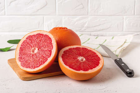 Whole ripe grapefruit and two juicy halves on a cutting board and knife. Ingredient for fruit desserts. Tasty vegetarian food, slimming diet and vitamin healthy eating. Top view.