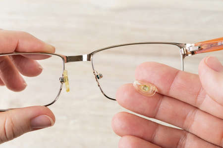Hands hold eyeglasses and nose pad broke off them against brown desk. Golden rim spectacles with damaged eye wires. Breakage of vision correction glasses for reading and computer work. Top view. 免版税图像