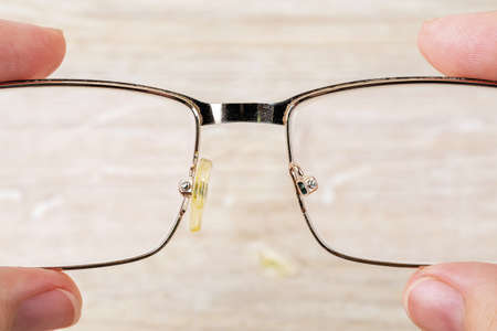 Fingers hold eyeglasses with one nose pad broke off them against brown desk. Golden rim spectacles with damaged eye wires. Breakage of vision correction glasses for reading and computer work. Close-up.