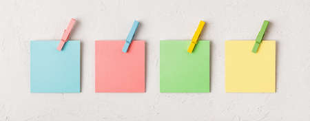 Four colorful blank notes every with wooden clothespin on a white concrete texture background. Plan tasks, share ideas, creativity concept. Copy space. Top view. 免版税图像