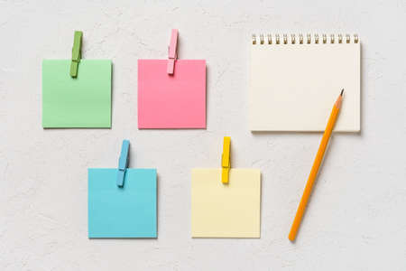 Four colorful blank  notes every with wooden clothespin and spring notepad with pensil on a white concrete background. Plan tasks, share ideas, creativity concept. Copy space. Top view.