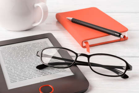 Eyeglasses on e-reader, orange note pad and cup on a white wooden desk. Vision correction glasses for reading and computer work. E-reading for pleasure and education. Front view. 免版税图像