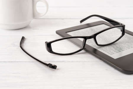 Eyeglasses with one temple broken off the rim on a e-reader over white wood desk. Breakage of vision correction glasses for reading, remote learning and computer work. Front view.