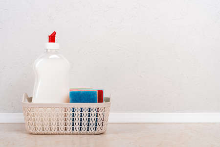 White dishwashing liquid and few foam sponges in a small basket on the kitchen table against white concrete wall. Household kitchen detergent. Copy space. Front view. 免版税图像