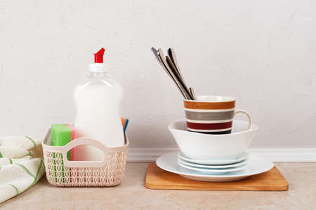 White dishwashing liquid and few foam sponges in a small basket near a stack of clean dishes on the kitchen table against white concrete wall. Household kitchen detergent. Front view.