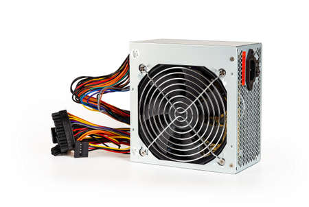New power supply unit with fan grill, colorful wires with connectors, On Off button and  power cord socket  isolated on white background. Personal computer PSU replasing, hardware equipment. Close-up. 免版税图像