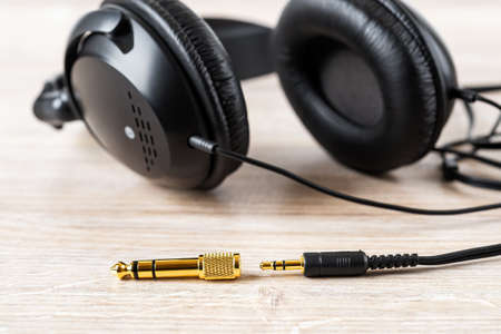 Golden TRS adapter and jack near black wired over ear headphones on a desk. Gold plated plugs for high quality audio. Modern personal gadget for listening to music. Close-up.
