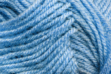 Cropped skein of pale blue woolen knitting thread texture. Ball of soft woolen yarn full frame macro photography. Knitting threads for handicraft and home hobbies background. Close-up design element. Front  view.