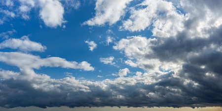 Storm is coming. Dark gray stormy clouds covering bright blue sky with fluffy white clouds. Changing weather from clear sunny to rainy overcast. Dramatic cloudscape panorama. Weather forecast, meteorology. 免版税图像