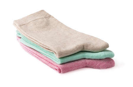 Stack of new tall colorful socks isolated on a white background. Three pairs of beige, green and pink socks folded in half. Elastic cotton hosiery. Full depth of field. Front view. 免版税图像