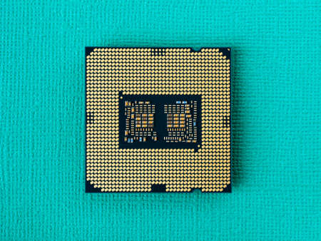 Pc micro CPU with gold plated contacts on a textured turquoise background. Modern central processing unit close-up. Desktop computer hardware components for assembly, upgrade and repair. Macro. Top view.