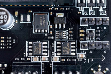 Varna, Bulgaria, January 08, 2021. Electronic circuit board with microchips and other components on a modern black motherboard. Computer mainboard circuit components. Desktop hardware macro.