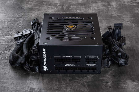 Varna, Bulgaria, January 11, 2021. Cougar GEX 80 Plus Gold certified PSU and set of power cords on a dark background. 850W modular power supply unit with flawless power delivery. PC hardware component.