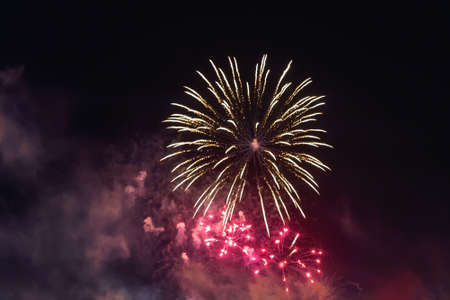 Bright red fireworks lights in the night sky. Small city celebrates new year with colorful fireworks. Firework smoke cloud in the sky. Outdoor night scene. Festive mood and holidays. Real life.