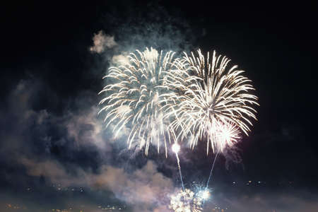 Bright white fireworks lights in the dark sky. Small city celebrates new year with colorful fireworks at night. Gray firework smoke cloud in the sky. Festive outdoor night scene. Holidays. Real life.