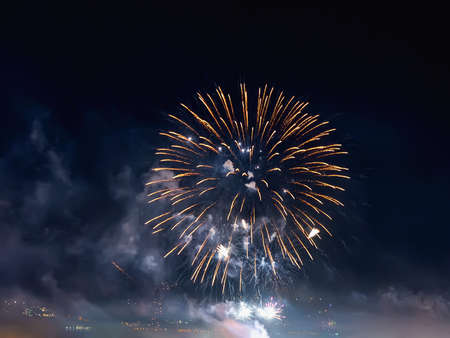 Bright yellow fireworks sparks in the dark sky. Small city celebrates new year with colorful fireworks at night. Gray blue firework smoke cloud in the sky. Festive outdoor night scene. Holidays. Real life. 免版税图像