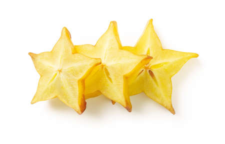Three slices of juicy carambola or star fruit isolated on white background. Ingredient for cocktails, salads and fruit desserts. Delicious vegetarian food and vitamin low calorie healthy eating. Top view. 免版税图像