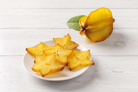 Sliсes of juicy carambola on a saucer and one whole ripe star fruit over white wood table. Ingredient for cocktails, salads and fruit desserts. Tasty vegetarian food and vitamin low calorie healthy eating. Front view.