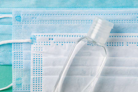 Close-up of hand sanitizer in a small bottle on a disposable medical face masks. Personal protection against viral infections, virus and flu. Healh care concept. Top view.