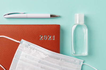 2021 year red leather diary, pen, small bottle of hand sanitizer and disposable medical face mask on a pale turquoise background. Planning your life and business considering the epidemic. Top view.