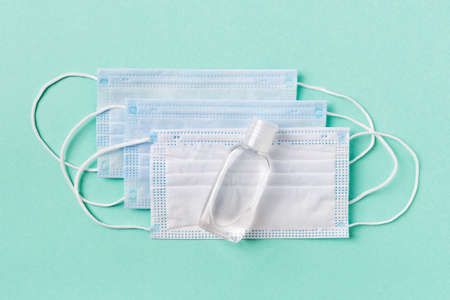 Disinfecting hand sanitizer in a small bottle on a disposable medical face masks on a pale turquoise background. Personal protection against viral infections, virus and flu. Healh care. Top view. 免版税图像