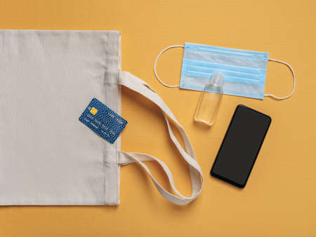 Credit card on a cotton grocery bag, smartphone with copy space on the screen, hand sanitizer and disposable face mask a yellow background. Protection against virus and flu when going outside. Top view.