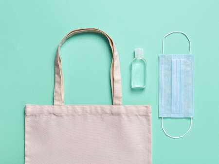 Eco-friendly cotton grocery bag, hand sanitizer in a small bottle and medical face mask on a green background. Protection against viral infections, virus and flu when going outside. Top view.