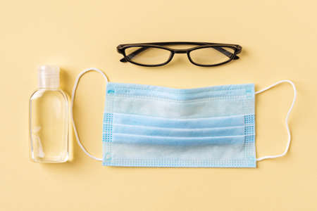 Disposable medical face mask, hand sanitizer in a small bottle and glasses on a yellow background. Personal protection against viral infections, virus and flu. Healh care. Top view. 免版税图像
