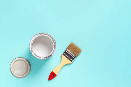 Paint brush with wooden handle and open white paint can on a cyan blue background. Construction painting work, repair and redecorate concepts. Top view.