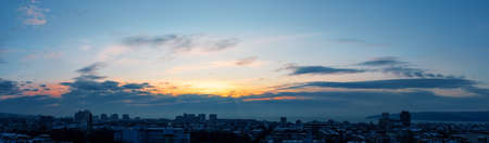 Early morning winter sky just before the sunrise over small seashore town. Golden dawn lights up in the sky over a sleeping city. Panoramic landscape with urban skyline. Scenic skyscape. 免版税图像